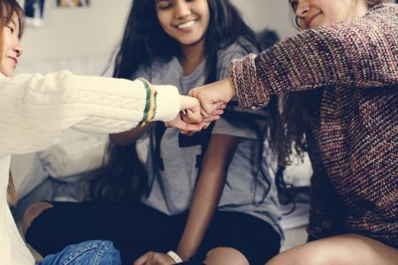 Teenage girls in a bedroom fist bumping friendship concept